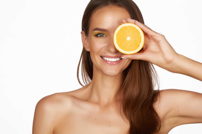 美女微笑着拿着橙子