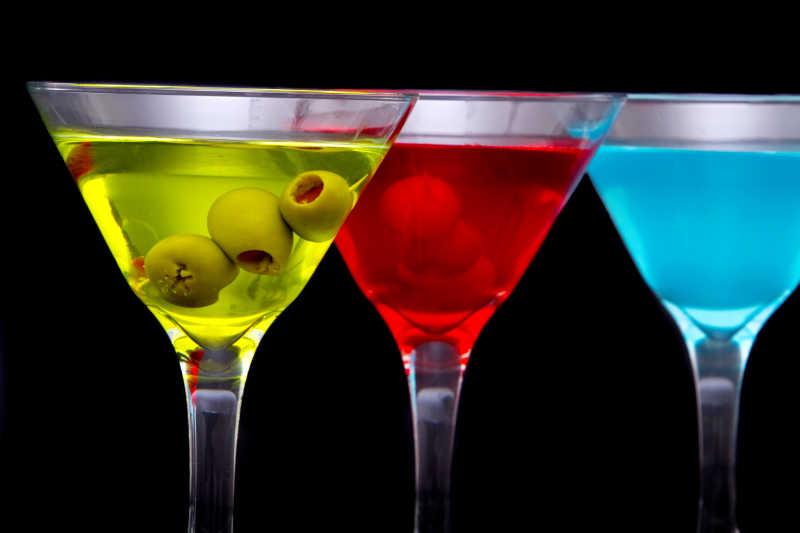 黑色背景下的三种颜色的鸡尾酒酒杯