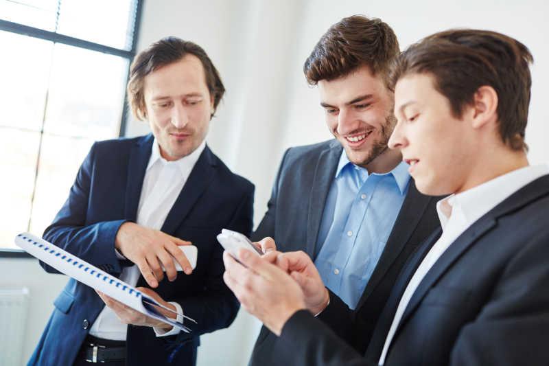 三个男性商务人士正在一起看手机短信