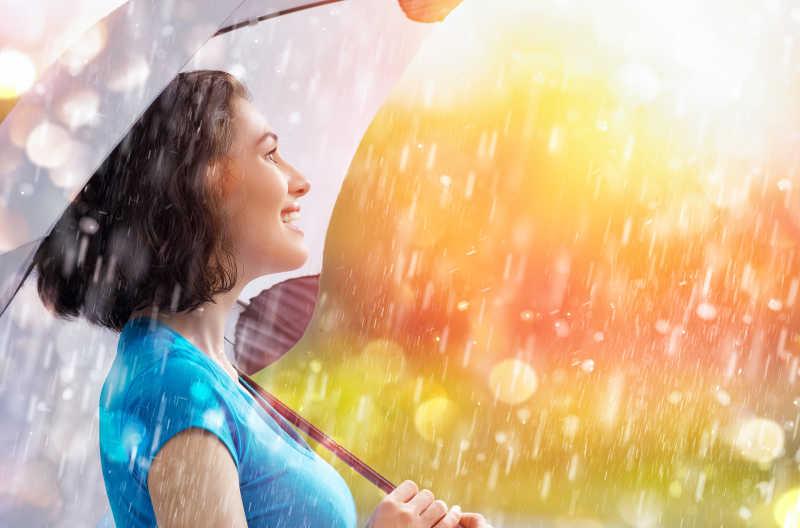 微笑的女人打着伞面对幸福的雨