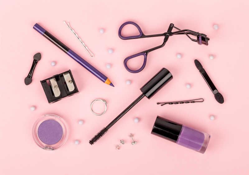 粉红色背景的专业套装化妆品及工具