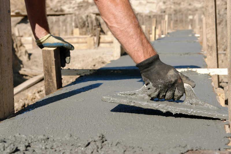 用铁铲铺平混凝土拌合物