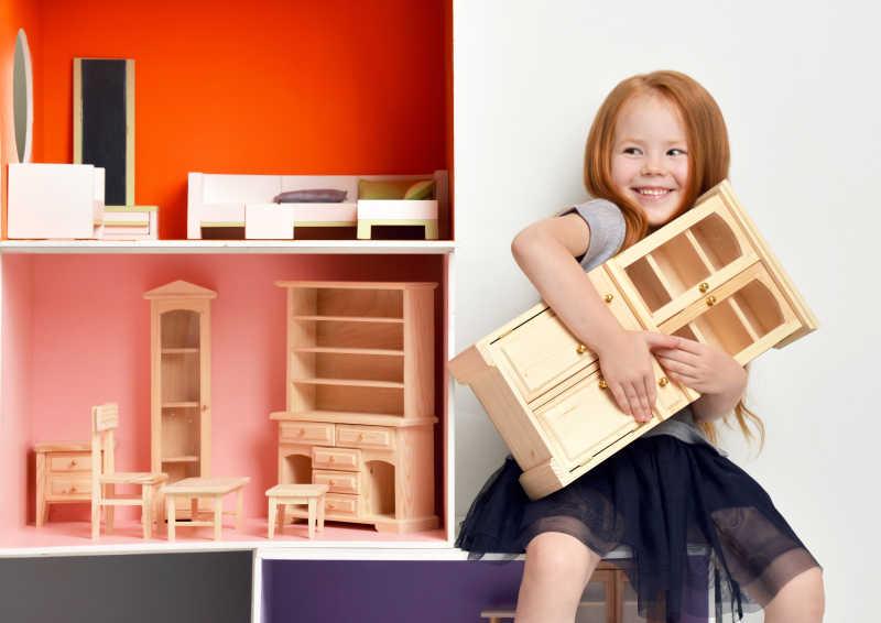 抱着小型积木柜子的快乐的小女孩