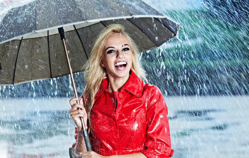 站在雨里的穿着红色皮衣举着伞的大笑的女性