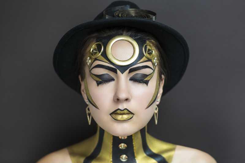 灰色背景上的黑色金色艺术彩妆特写