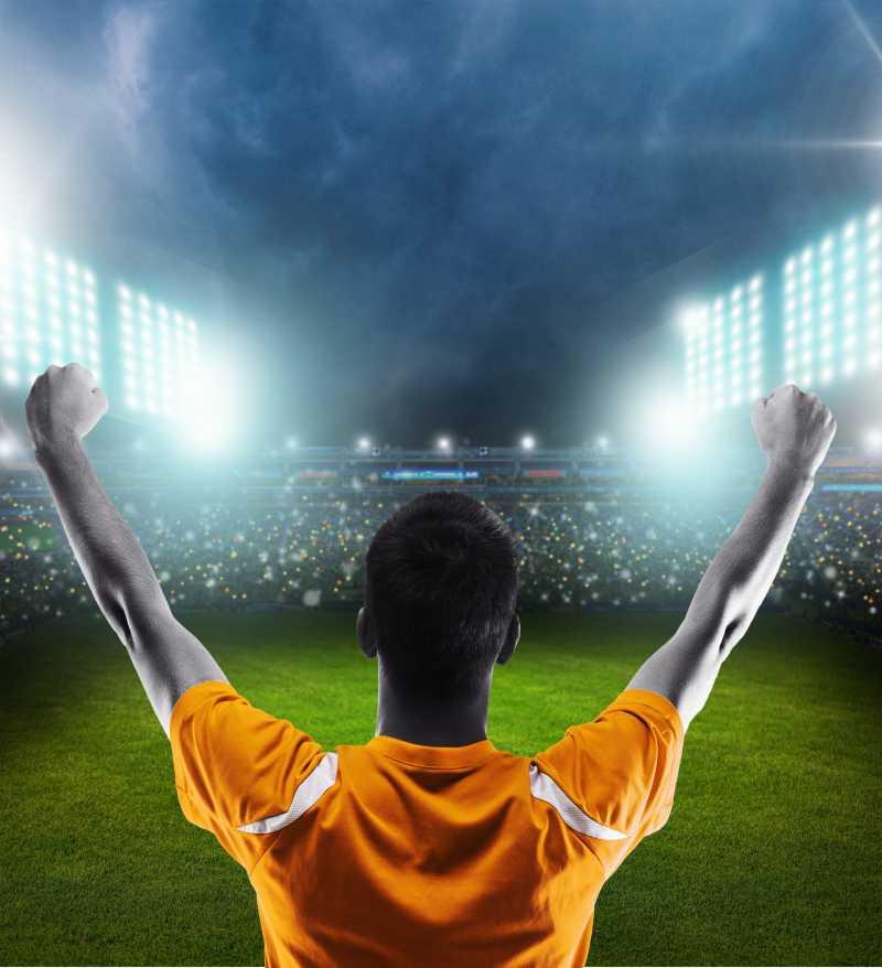 灯光下欢呼加油的足球运动员