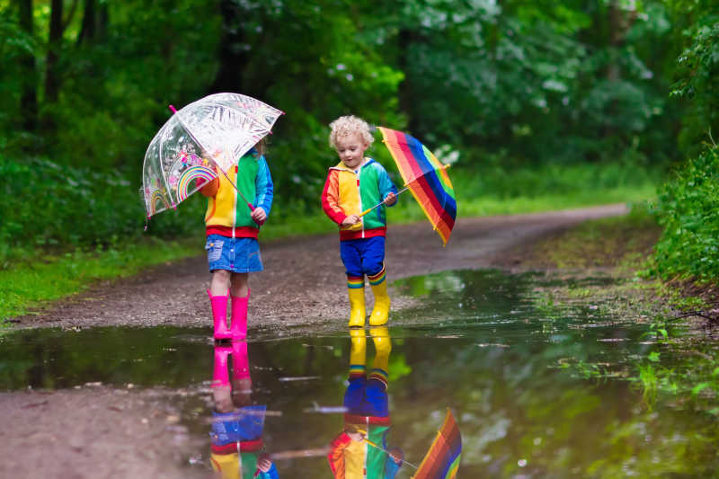 小男孩和女孩在多雨的夏季公园里玩耍