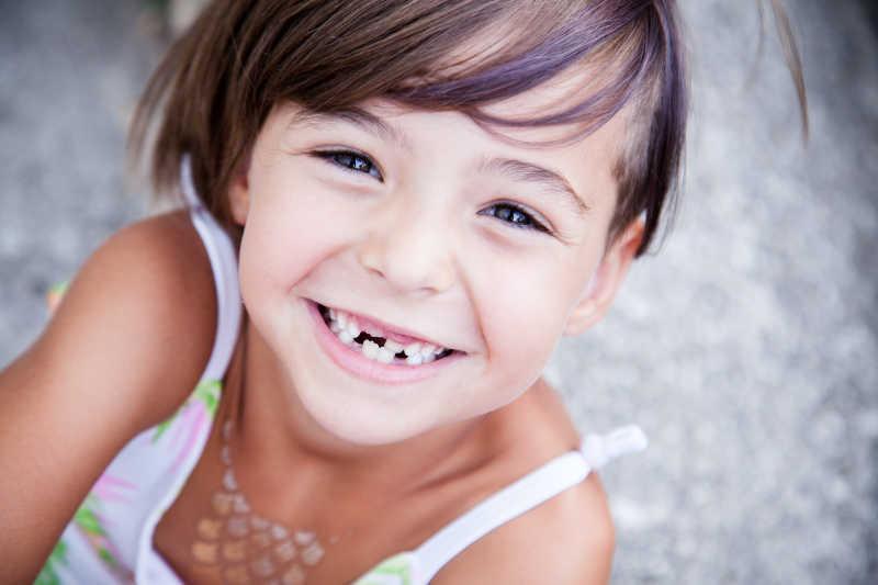 小女孩身上沾满了面粉摆出滑稽表情   绿板背景上一个可爱的小女孩