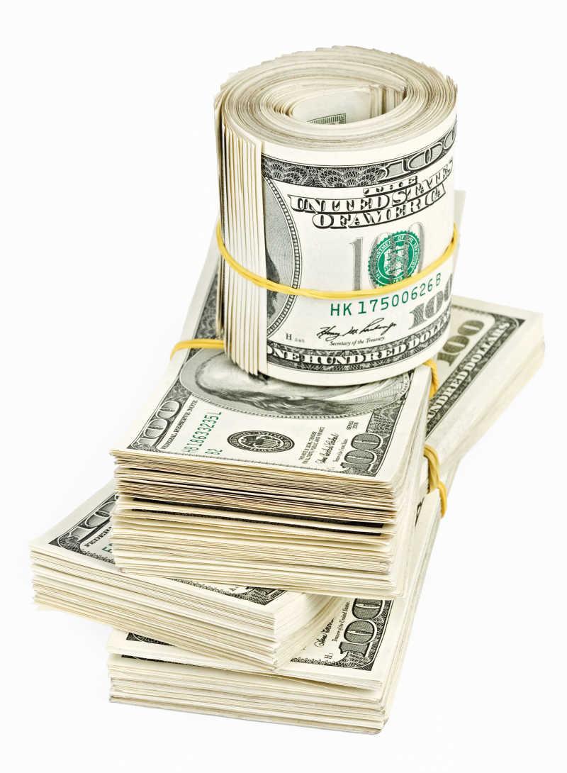 白色背景下的几沓美元钞票