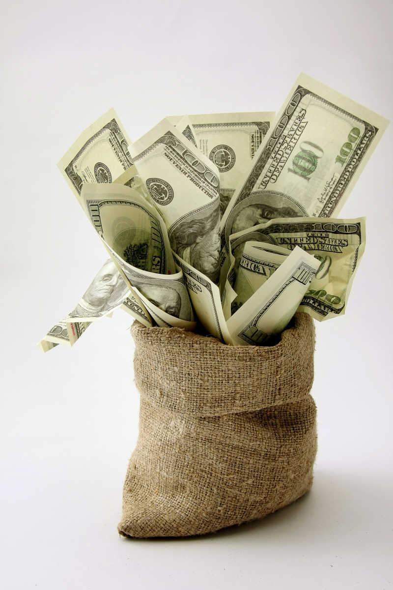 白色背景下的装在帆布钱袋里的美元现金