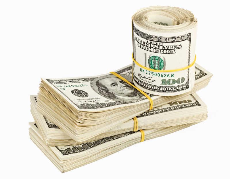 白色背景下的几卷美元钞票