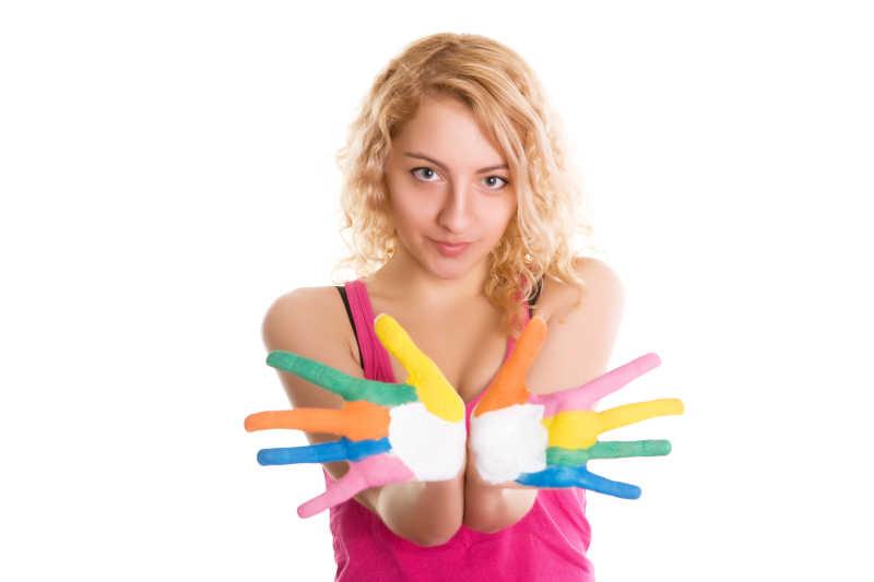 白色背景下双手涂满五颜六色颜料的美女