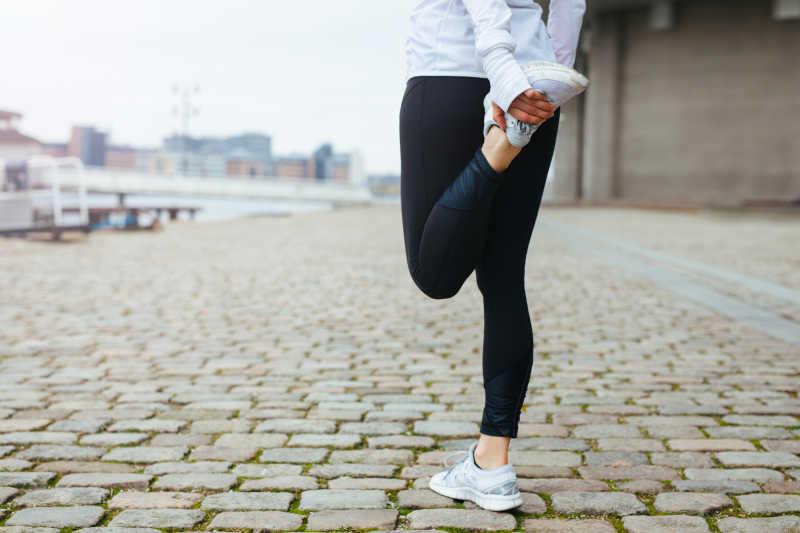 年轻女子在城市街道做跑步前伸展腿部运动
