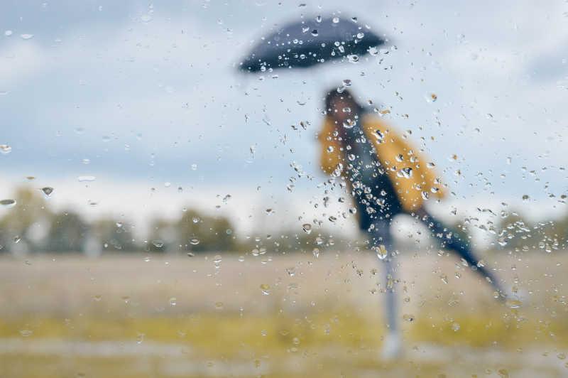下雨淋有雨滴的窗户后面的打着伞的女孩