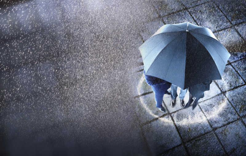 下雨的天气里三位商人围在一把雨伞躲雨