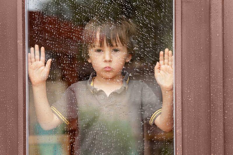 小男孩透过窗户看着外面的下雨天