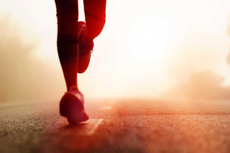 昏暗的阳光下在公路上跑步运动员的脚部特写