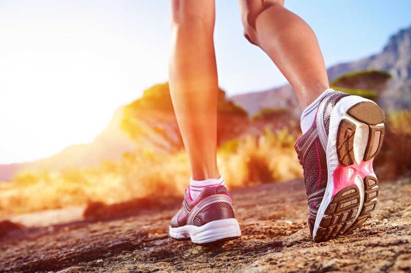 黄昏阳光下跑步女子的脚部特写
