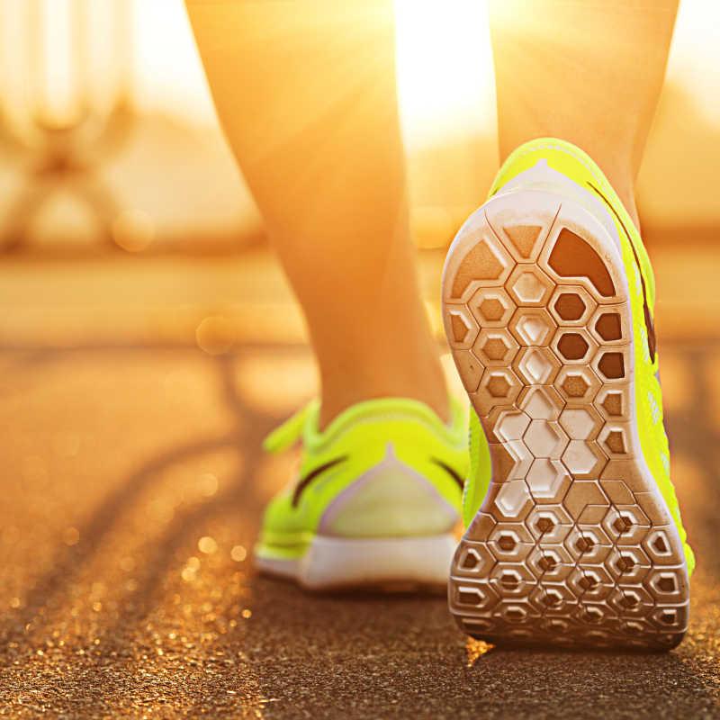 清晨阳光下穿着运动鞋跑步的人