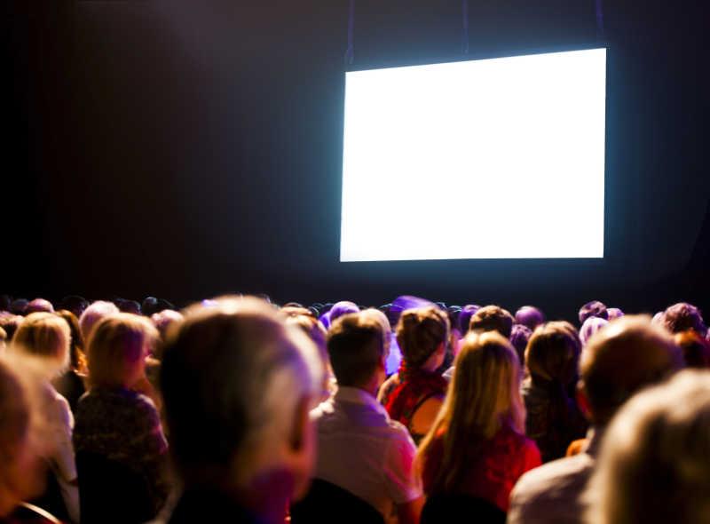 观众在黑暗中看着明亮的屏幕