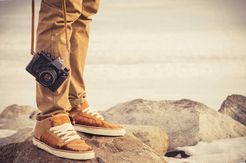 石头上男人的腿和老式相机特写