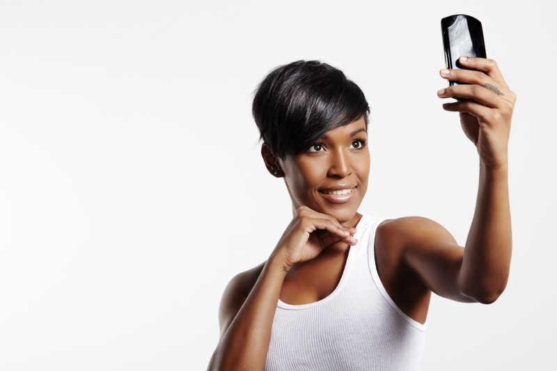 白色背景下手机自拍的女人