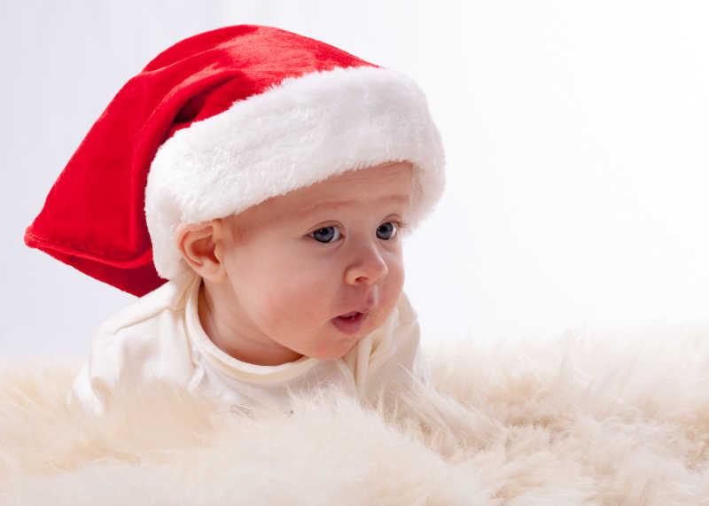 毛毯上戴着圣诞帽的可爱孩子
