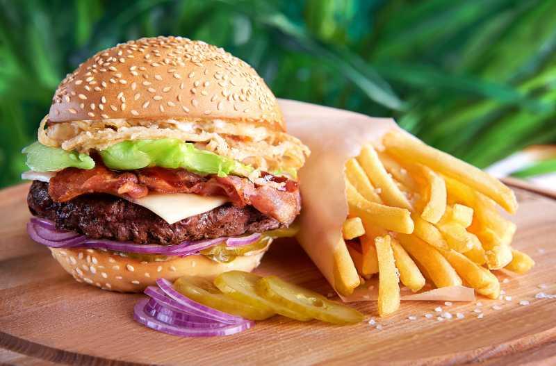 砧板上的快餐汉堡包和薯条热狗