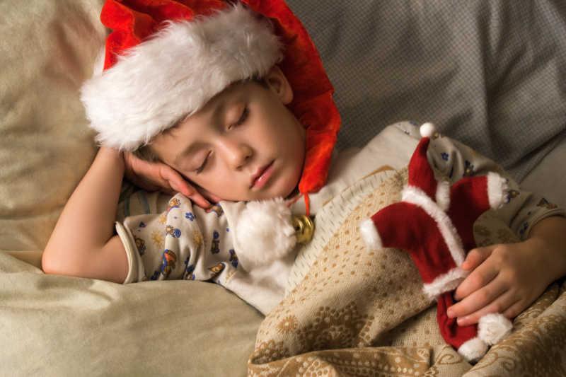 戴着圣诞帽睡着的可爱儿童