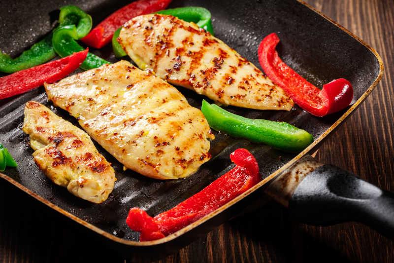 木桌上黑色盘子里的烤好的鸡胸肉和菜椒