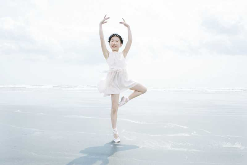 穿着白色连衣裙的跳舞小女孩