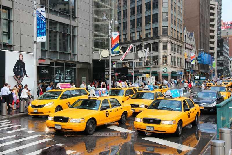 人们在纽约的第八大道乘坐黄色出租车