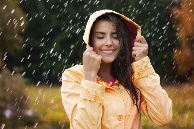戴着帽子站在雨中的女性