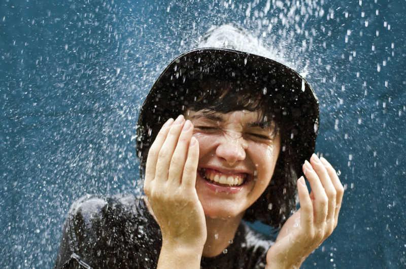 戴着帽子在雨中淋雨的年轻女性