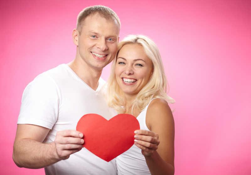 粉色背景下幸福年轻夫妻手拿红色的纸心的画像