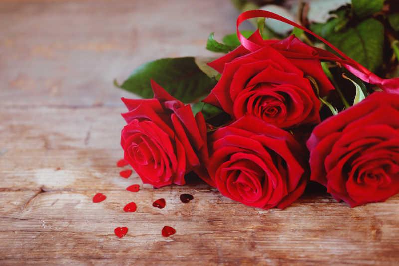 木桌上红色的玫瑰花和散落的心形剪纸