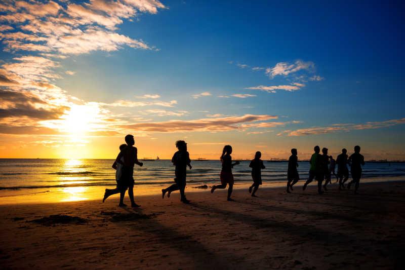 一群年轻人在美丽的夏天在海滩上跑步