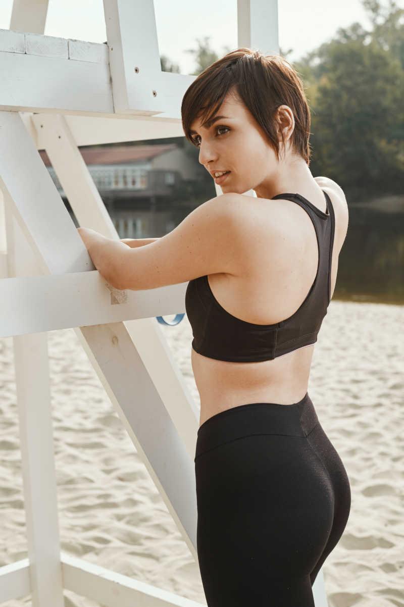 可爱的黑发美女在秋天的河滩健身