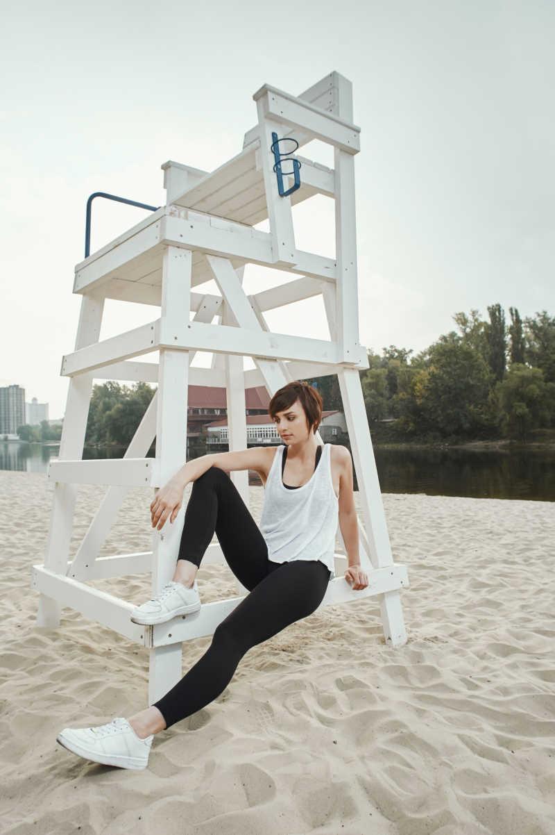 在秋天的河滩可爱的黑发在黑色运动装美女