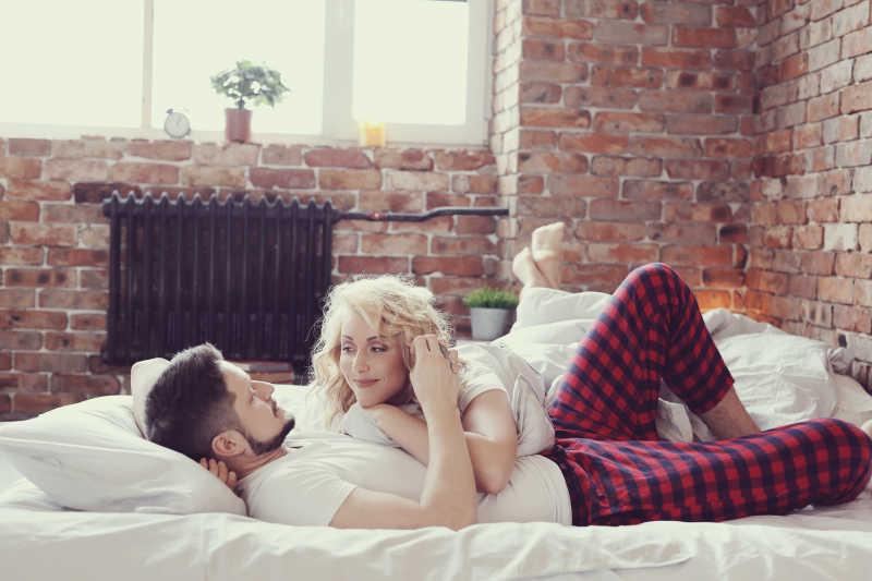 美丽的妻子趴在躺在床上的丈夫身上