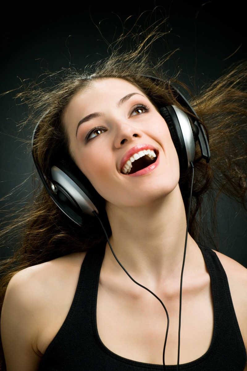 戴着耳机听音乐的美女图片素材_白色背景下戴着耳机听