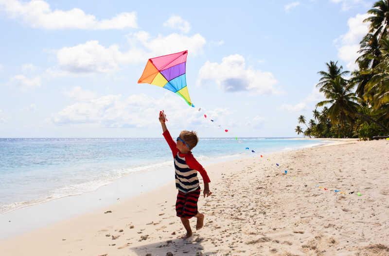 在热带海滩上放风筝的小男孩