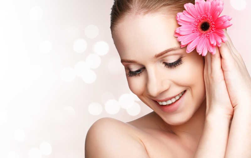 戴着一朵粉色非洲菊的美丽自然女孩肖像