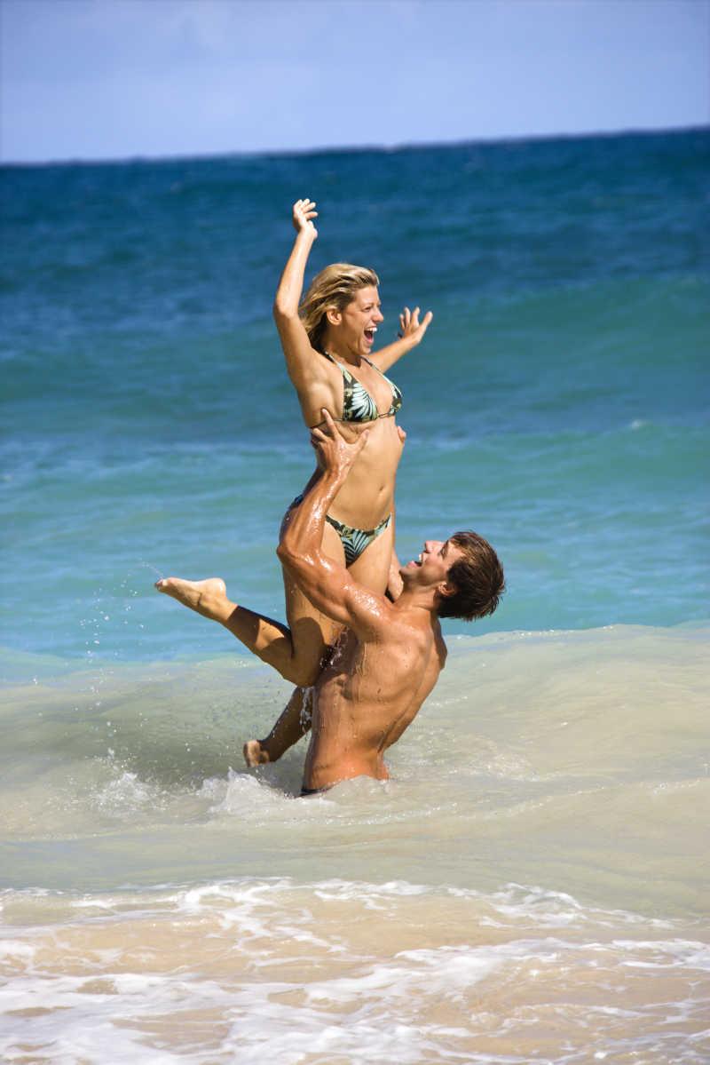 在水中央举起妻子的年轻丈夫