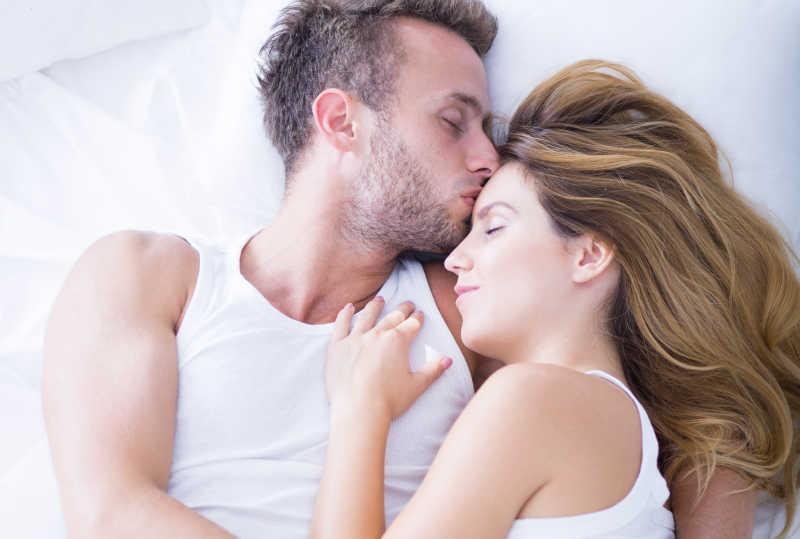 在床上温柔地拥抱着的恩爱情侣