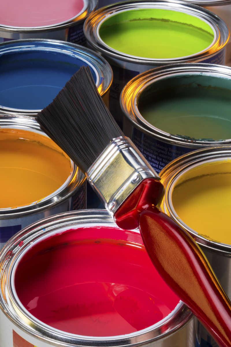 毛刷和罐子里各种颜色的涂料