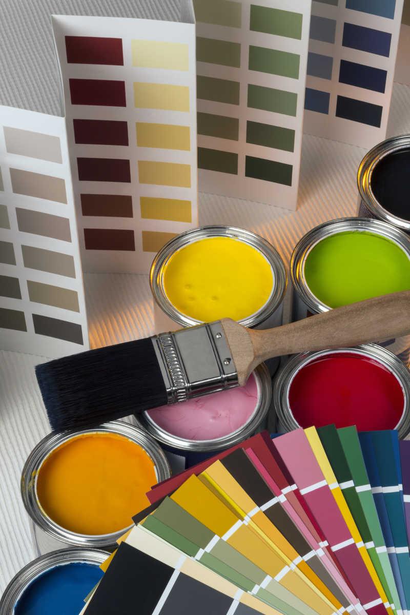 各种颜色卡纸和油漆罐上的毛刷