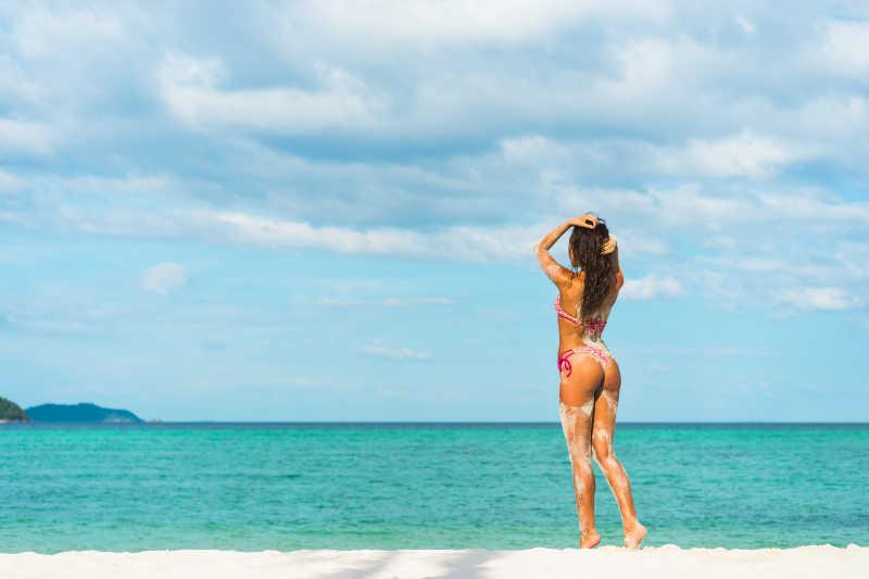 蓝天下蓝色的大海和金色沙滩上的比基尼美女