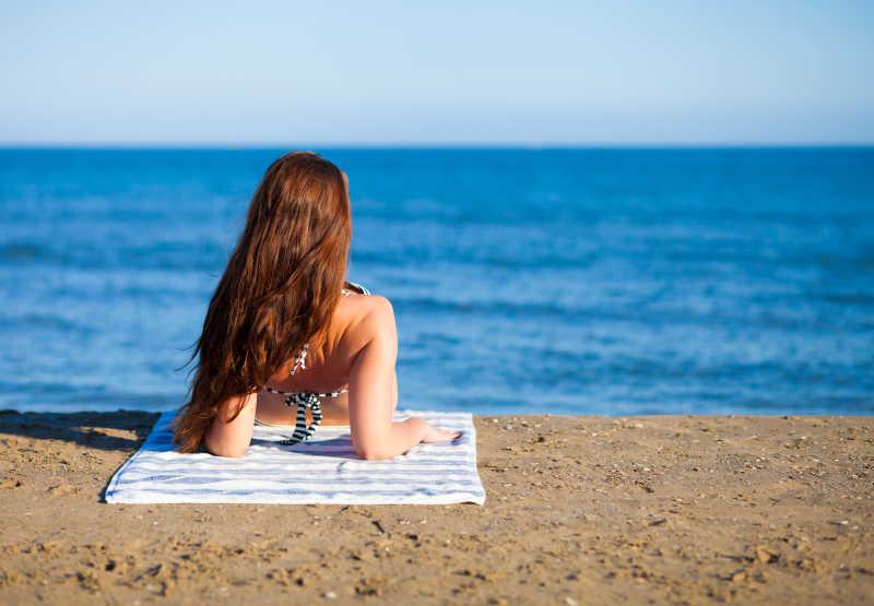 蓝色大海边沙滩上的比基尼美女背影