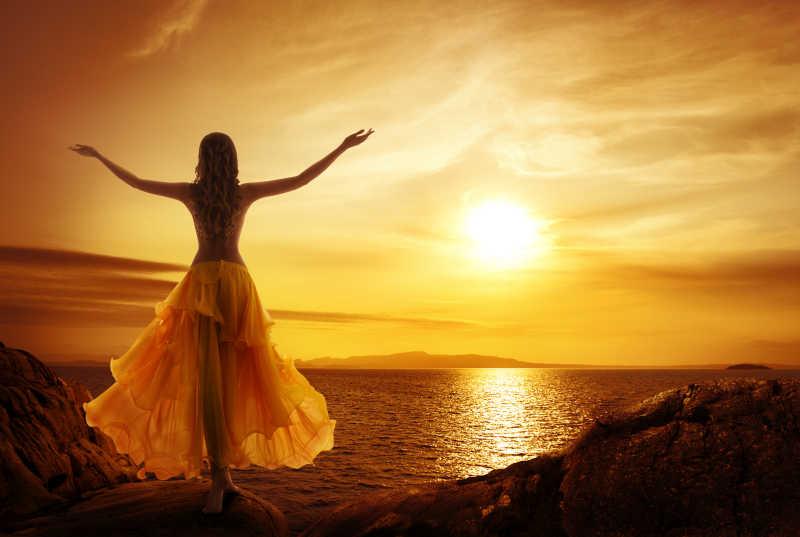 女人站在海边的石头张开双臂放松姿势